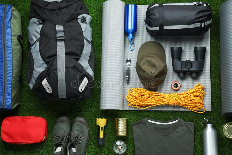 Flat lay composition with different camping equipment. On green grass royalty free stock images