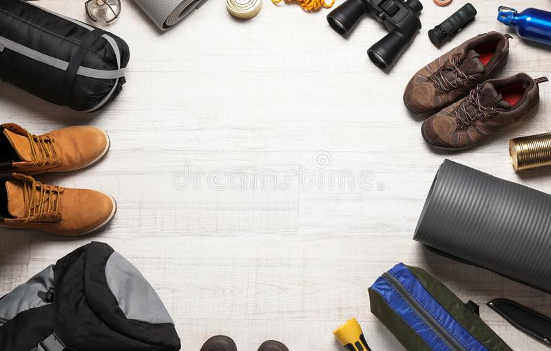 Flat lay composition with different camping equipment on wooden background. Space for text royalty free stock photo