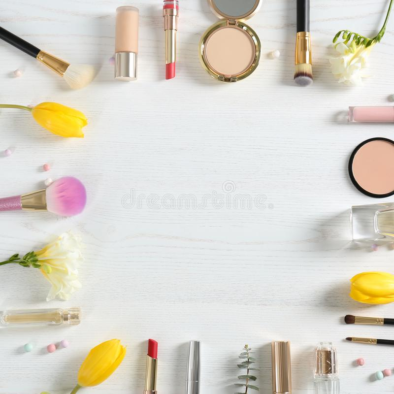 Flat lay composition with different decorative cosmetics and flowers on wooden table. Trendy makeup products stock images