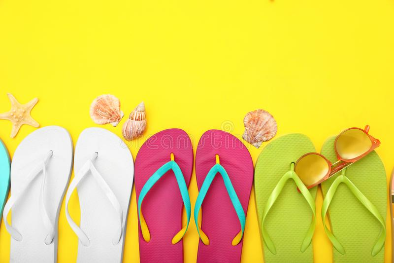 Flat lay composition with different flip flops on yellow background. Summer beach accessories. Flat lay composition with different flip flops on yellow royalty free stock photo