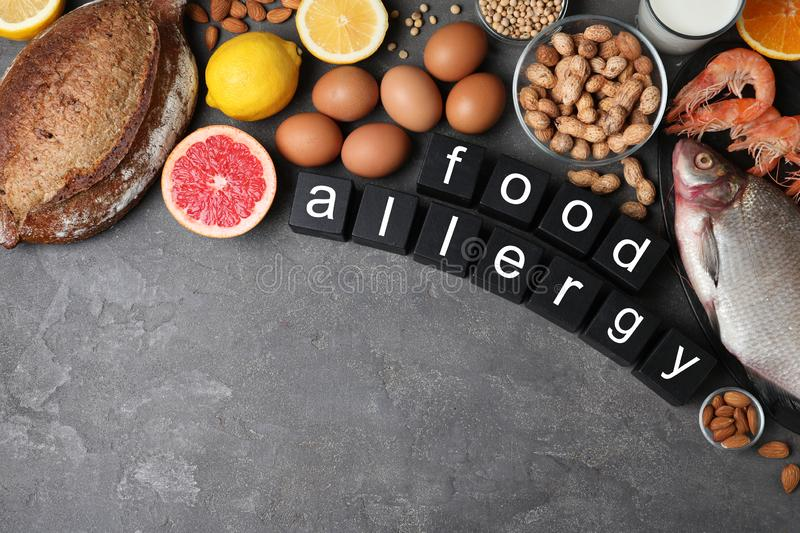Flat lay composition of different products and black cubes with words Food Allergy on grey table. Space for text royalty free stock photos
