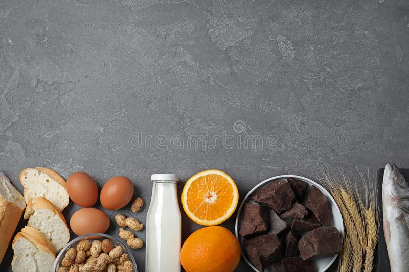Flat lay composition of different products on grey table. Food allergy concept. Flat lay composition of different products and space for text on grey table. Food royalty free stock images