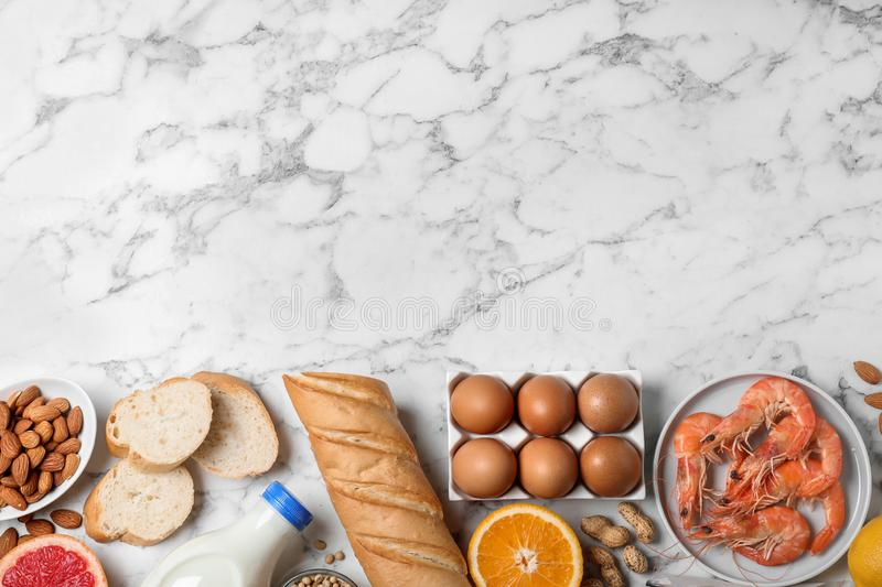 Flat lay composition of different products and space for text on marble table. Food allergy concept. Flat lay composition of different products and space for stock images