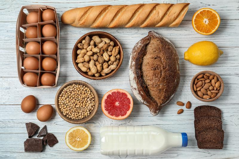 Flat lay composition of different products on wooden table. Food allergy concept. Flat lay composition of different products on white wooden table. Food allergy stock photography