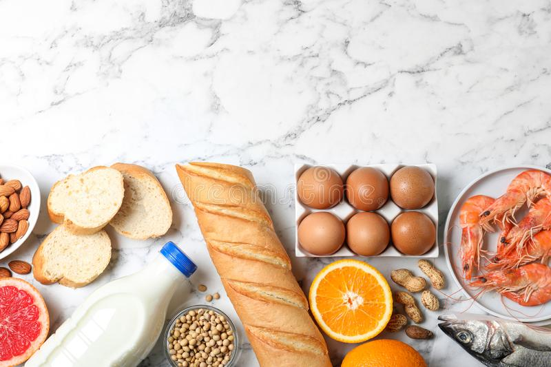Flat lay composition of different  and space for text on white marble table. Food allergy concept. Flat lay composition of different products and space for text royalty free stock photos