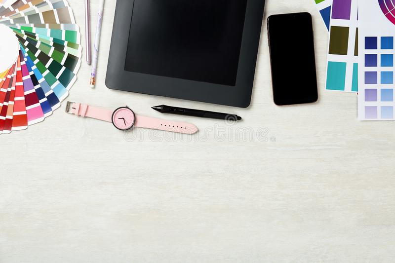 Flat lay composition with digital devices and color palettes on light background. Graphic designer`s workplace. Flat lay composition with digital devices and stock photography