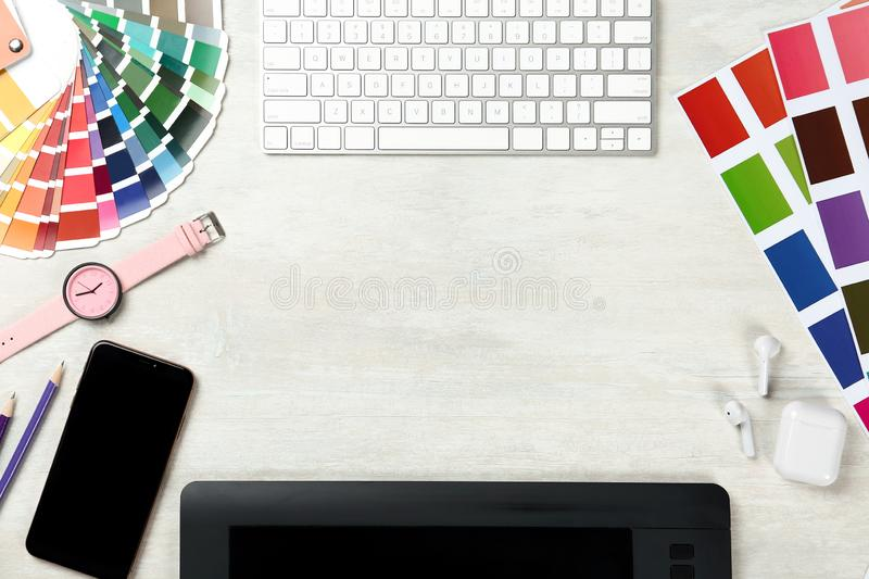 Flat lay composition with digital devices and color palettes on light background. Graphic designer`s workplace. Flat lay composition with digital devices and stock photos