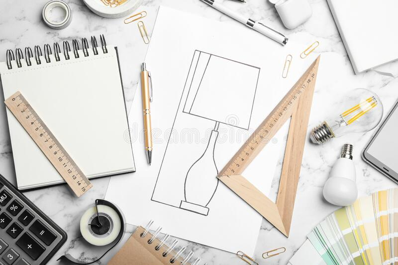 Flat lay composition with drawing of lamp on  marble table. Designer`s workplace. Flat lay composition with drawing of lamp on white marble table. Designer`s royalty free stock photography