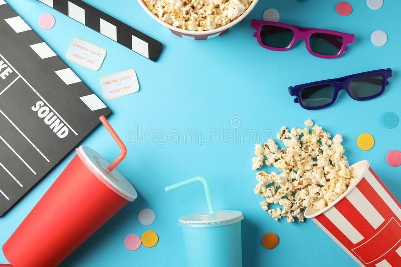 Flat lay composition with drinks, popcorn, 3d glasses, clapperboard, tickets on blue background. Copy space stock photos