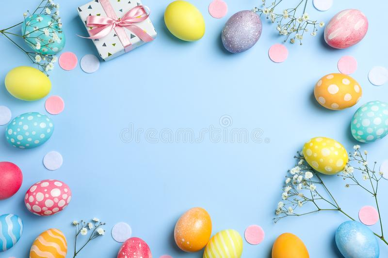 Flat lay composition with Easter eggs, present and flowers on color background, space for text. Top view stock photo