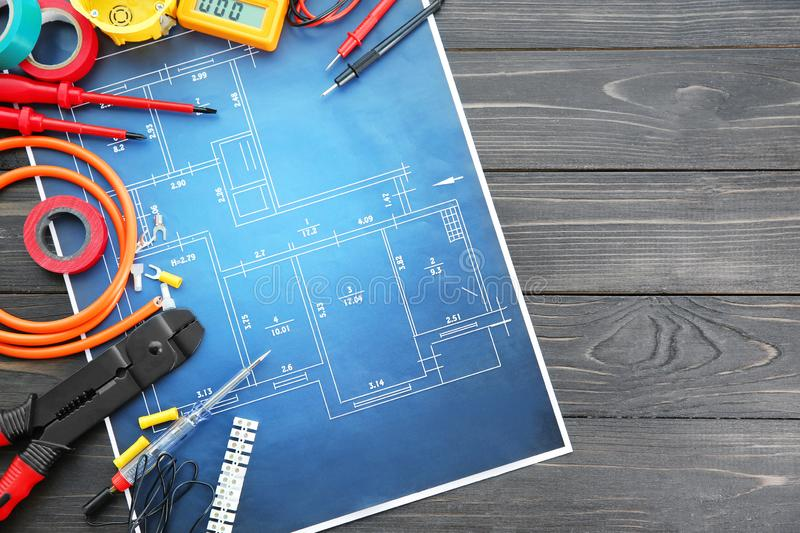 Flat lay composition with electrical tools and house plan on wooden background stock image