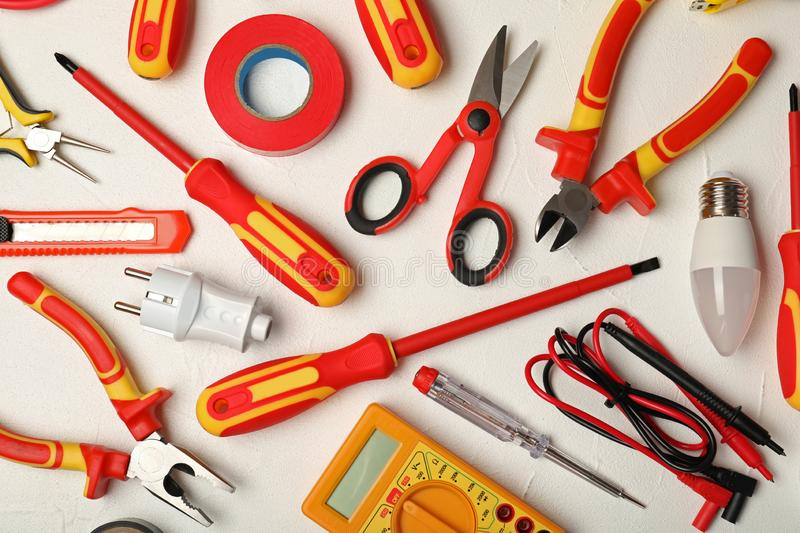 Flat lay composition with electrician`s tools. On light background stock photography