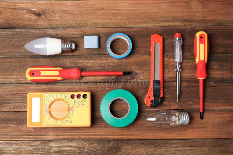 Flat lay composition with electrician`s tools. On wooden background stock images