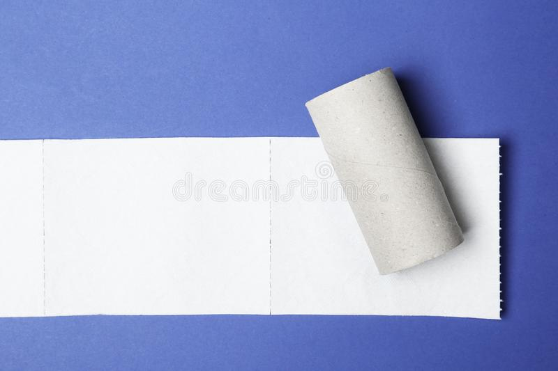 Flat lay composition with empty roll and toilet paper on color background. Space for text stock images