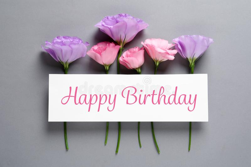Flat lay composition of Eustoma flowers and card with greeting HAPPY BIRTHDAY. On grey background stock photography