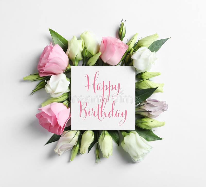 Flat lay composition of Eustoma flowers and card with greeting HAPPY BIRTHDAY. On light background stock images