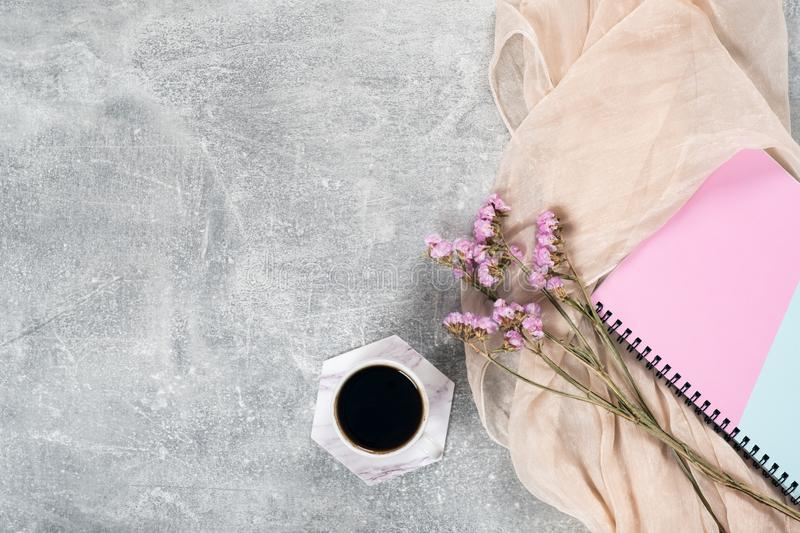 Flat lay composition with feminine scarf, coffee cup, pink dry flowers, paper notebook on concrete surface. Top view female home royalty free stock photos