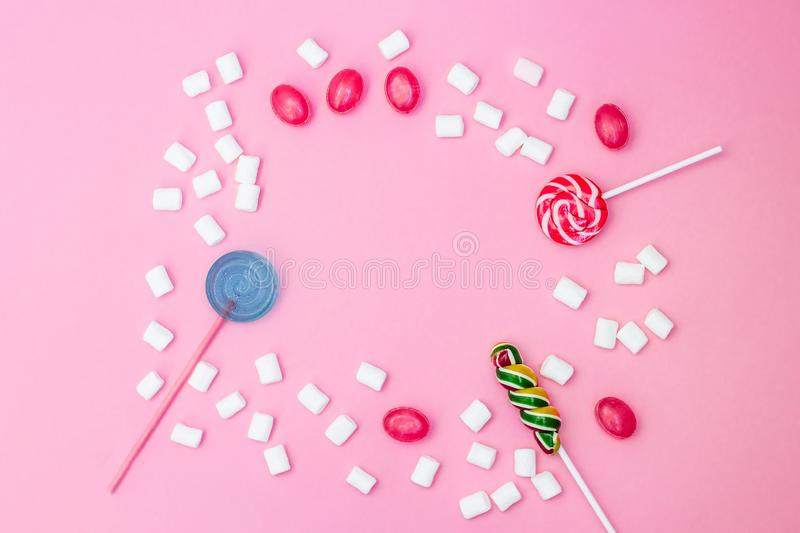 Flat lay composition with frame of lollipops and marshmallows and space for text on pink background royalty free stock photos