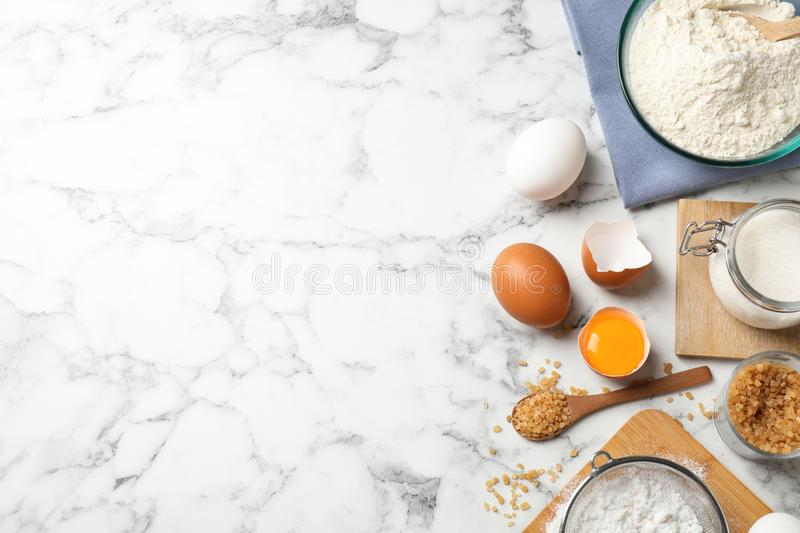 Flat lay composition with fresh ingredients for delicious homemade cake on white marble table. Space for text royalty free stock photo