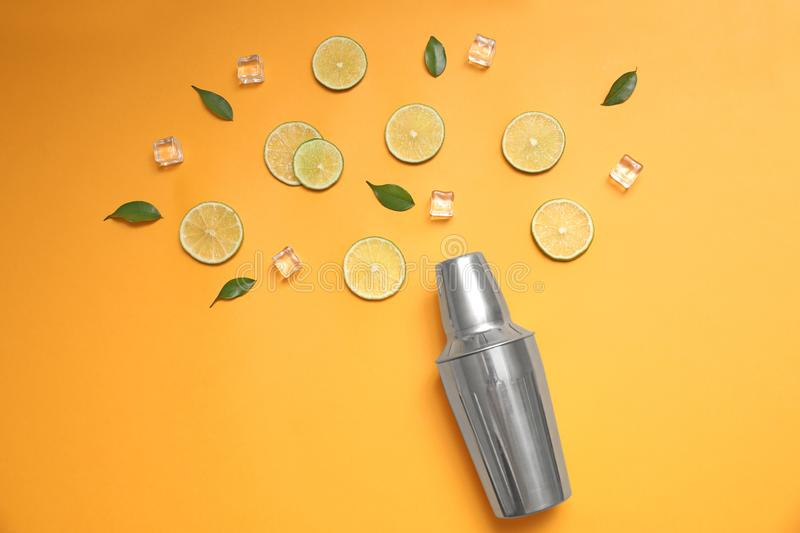 Flat lay composition with fresh juicy limes, ice cubes and cocktail shaker on yellow background. Flat lay composition with fresh juicy limes, ice cubes and stock images