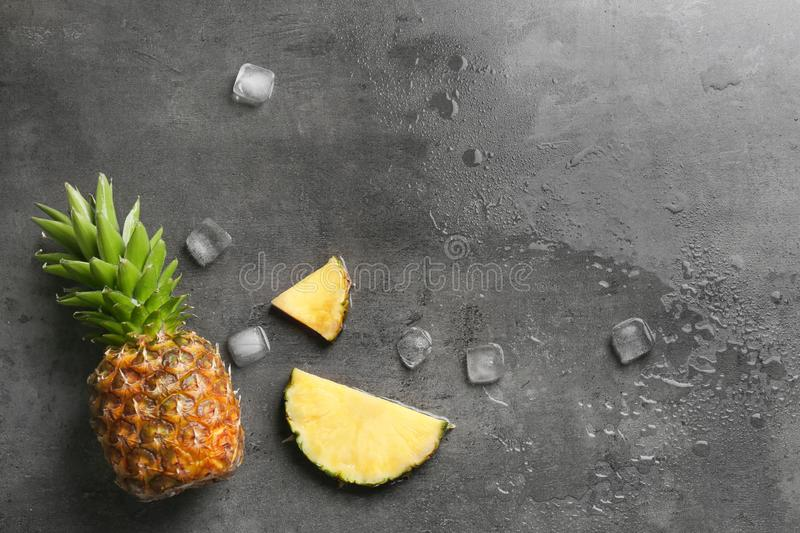 Flat lay composition with fresh pineapple and ice cubes on gray background stock photography