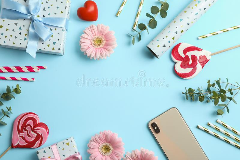 Flat lay composition with gerbera flowers, gift box and candies on blue background royalty free stock photo