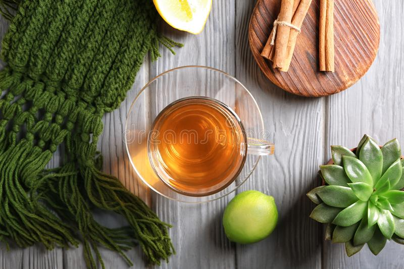 Flat lay composition with glass cup of tea, lime and cinnamon on wooden table stock photo