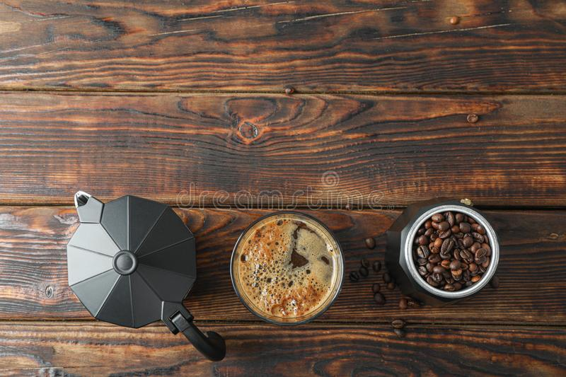 Flat lay composition with glass of fresh coffee, coffee maker and coffee beans on wooden table. Space for text stock photography