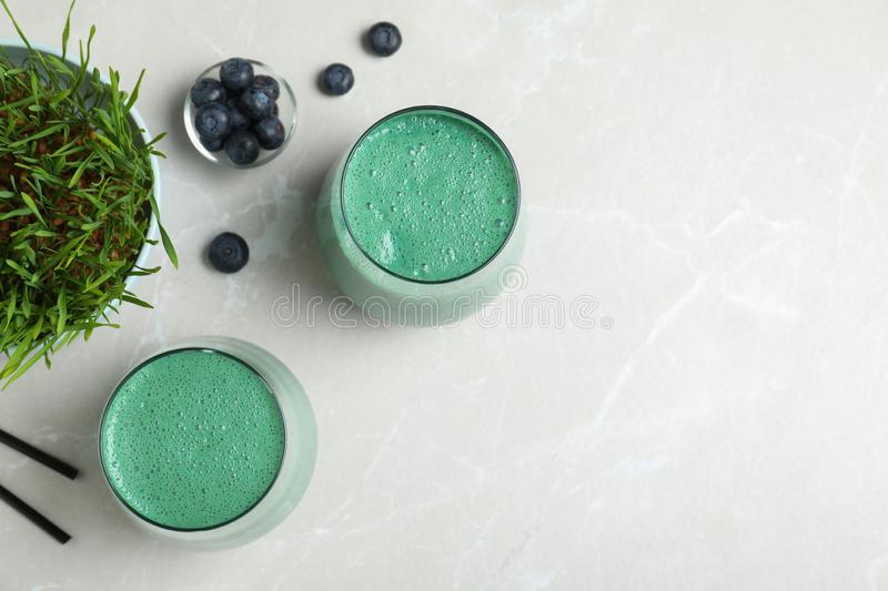 Flat lay composition with glasses of spirulina smoothie, wheat grass and blueberries on light background. Space for text stock photos