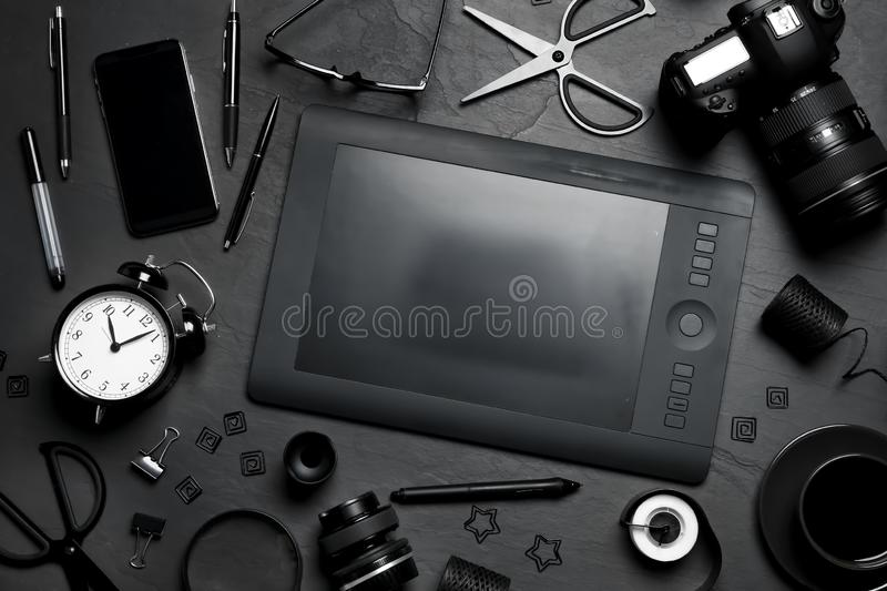Flat lay composition with graphic drawing tablet and office items on black table. Designer`s workplace. Flat lay composition with graphic drawing tablet and royalty free stock photos