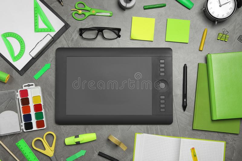Flat lay composition with graphic drawing tablet and office items on grey stone background. Designer`s workplace. Flat lay composition with graphic drawing stock photos