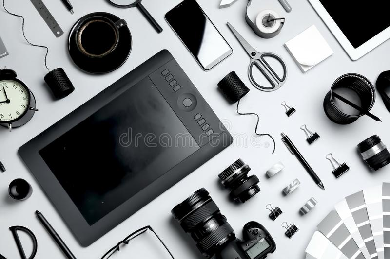 Flat lay composition with graphic drawing tablet and office items on light background. Designer`s workplace. Flat lay composition with graphic drawing tablet and stock photo