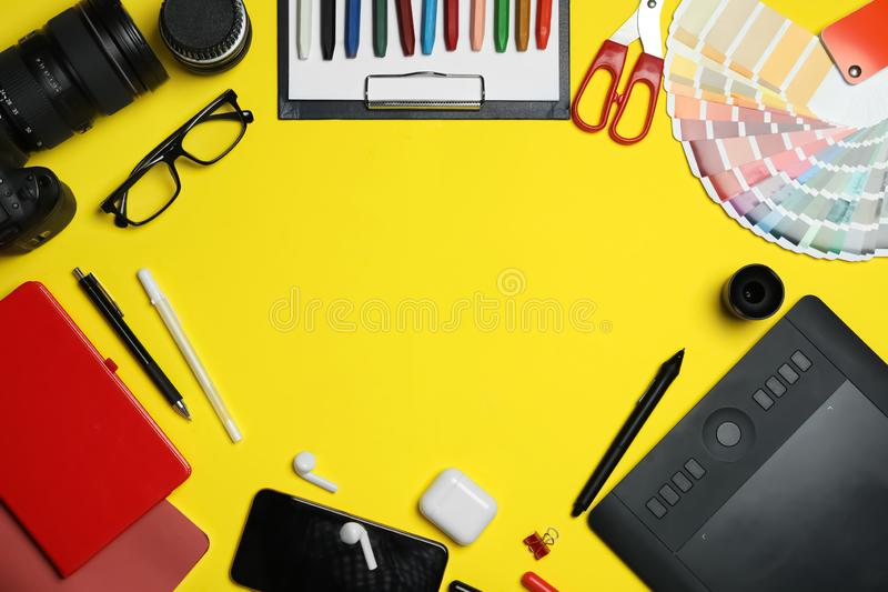 Flat lay composition with graphic drawing tablet and office items on yellow background, space for text. Designer`s. Flat lay composition with graphic drawing royalty free stock photo