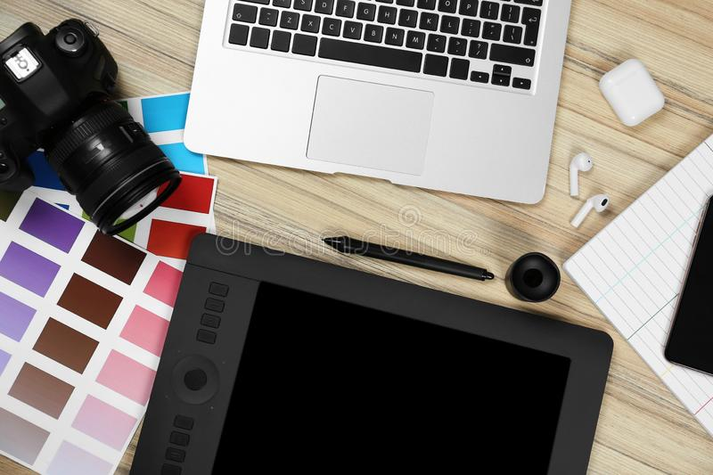 Flat lay composition with graphic tablet, camera and color palettes on table, space for text. Designer`s workplace. Flat lay composition with graphic tablet stock photo