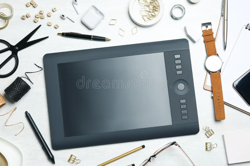 Flat lay composition with graphics tablet, stationery and accessories on table. Designer`s workplace. Flat lay composition with graphics tablet, stationery and stock photography