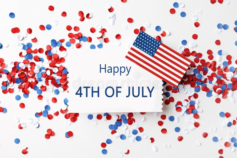 Flat lay composition with greeting card, USA flag and confetti. Happy Independence Day. Flat lay composition with greeting card, USA flag and confetti on white stock photography