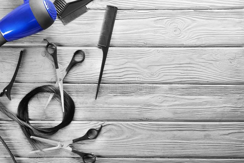 Flat lay composition with hairdresser's tools and strand of black hair on wooden background stock images