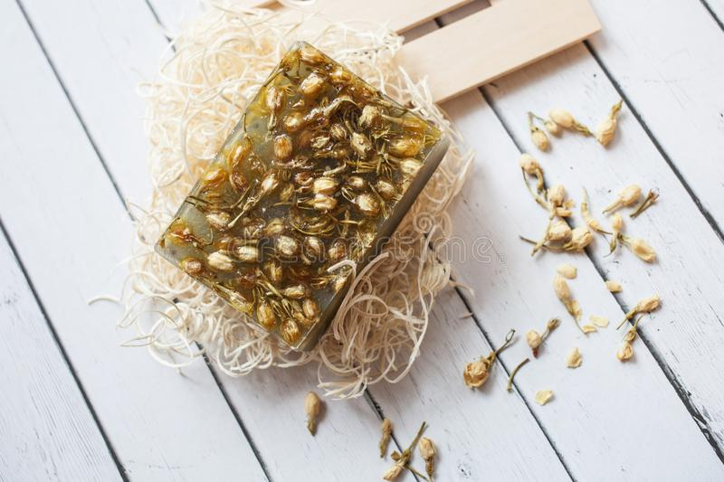 Flat lay composition with handmade soap bars with dried jasmine flowers and ingredients on white wooden background stock photos