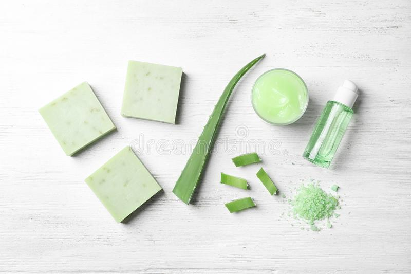 Flat lay composition with handmade soap bars and ingredients. On white wooden background stock image