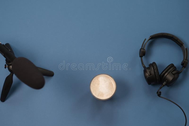 Flat lay composition with Headphones, microphone and coffee on a blue background. Podcast or webinar concept.  stock image