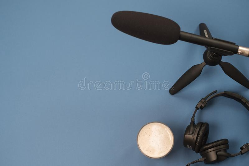 Flat lay composition with Headphones, microphone and coffee on a blue background. Podcast or webinar concept.  royalty free stock photography