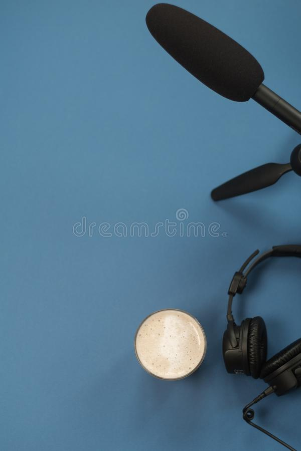 Flat lay composition with Headphones, microphone and coffee on a blue background. Podcast or webinar concept.  royalty free stock image