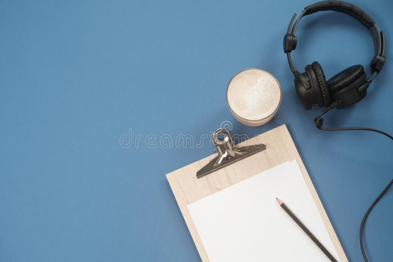 Flat lay composition with Headphones, microphone and coffee on a blue background. Podcast or webinar concept.  stock photography