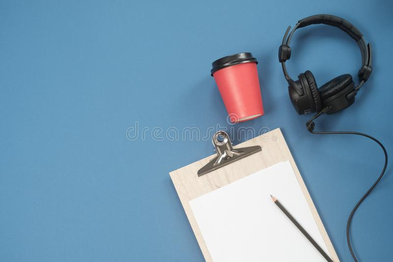 Flat lay composition with Headphones, microphone and coffee on a blue background. Podcast or webinar concept.  stock photo