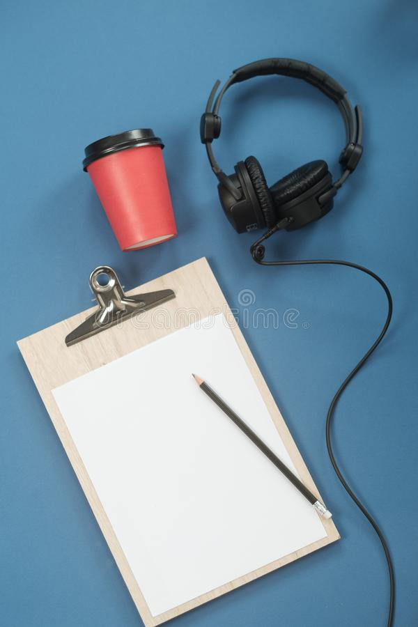 Flat lay composition with Headphones, microphone and coffee on a blue background. Podcast or webinar concept.  royalty free stock photos