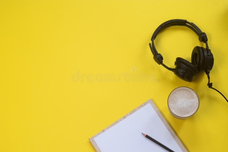 Flat lay composition with Headphones, microphone and coffee on a yellow background. Podcast or webinar concept.  stock photo