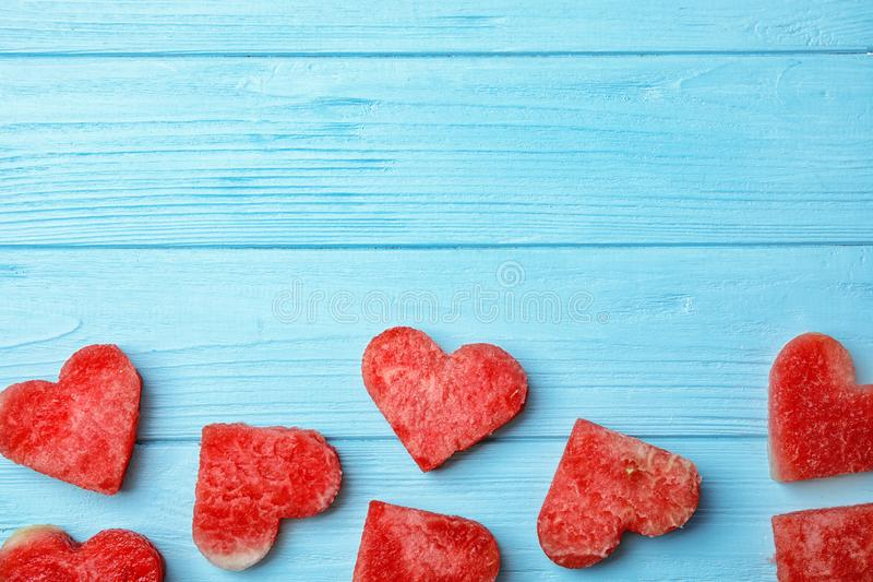 Flat lay composition with heart shaped watermelon slices. On wooden background royalty free stock photography