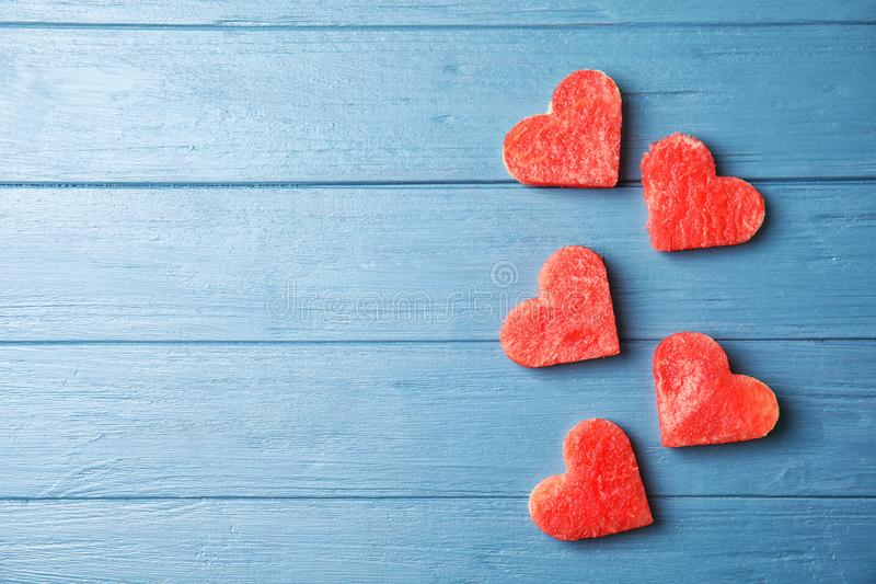 Flat lay composition with heart shaped watermelon slices. On wooden background stock image