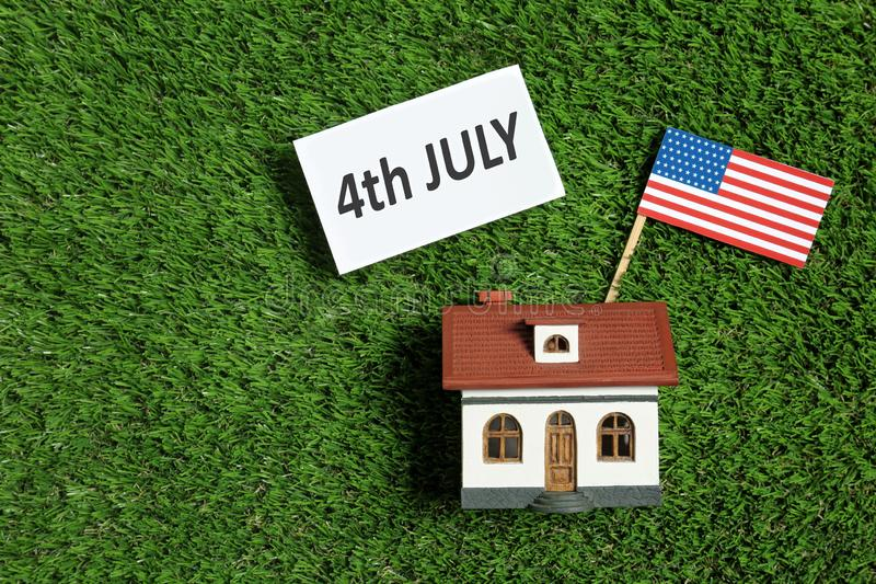 Flat lay composition with house model, USA flag and card on green grass. Happy Independence Day. Flat lay composition with house model, USA flag and card on stock photo