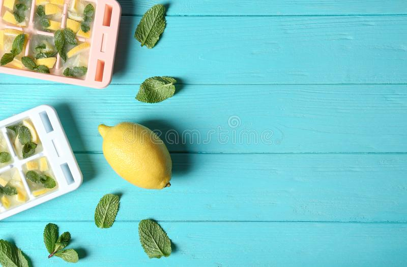 Flat lay composition with ice cube tray, mint and lemon on wooden background. Space for text stock images